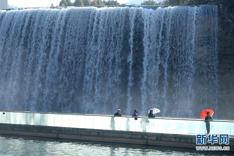 1月5日,游人在昆明瀑布公园参观游览。 当日,云南省昆明市阳光明媚,位于昆明市北部山水新区的昆明瀑布公园风景秀丽,吸引众多市民和游人前来休闲。公园内的人工瀑布落差约12.5米,宽幅约400米,充分利用牛栏江引水入滇工程而形成。 新华社记者秦晴摄