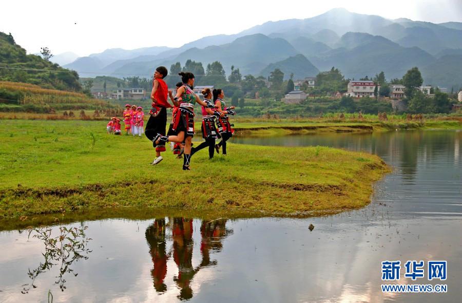 村民在水库边载歌载舞(6月20日摄)。新华网发(邓成斌 摄)