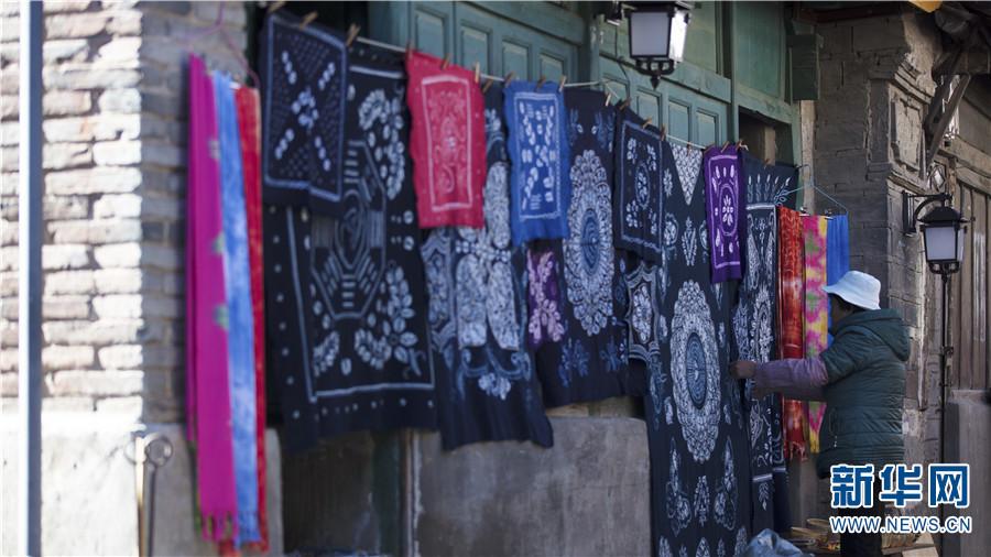 喜洲古镇,一位商户正在整理挂在墙上的扎染布(12月14日摄)。新华网 丁凝 摄